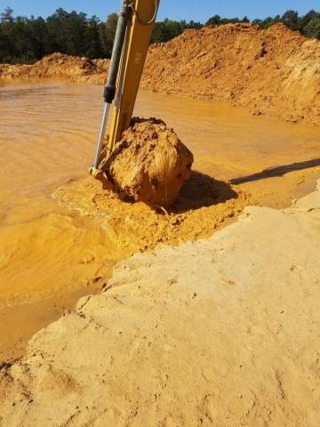 Pond being dug orange mud