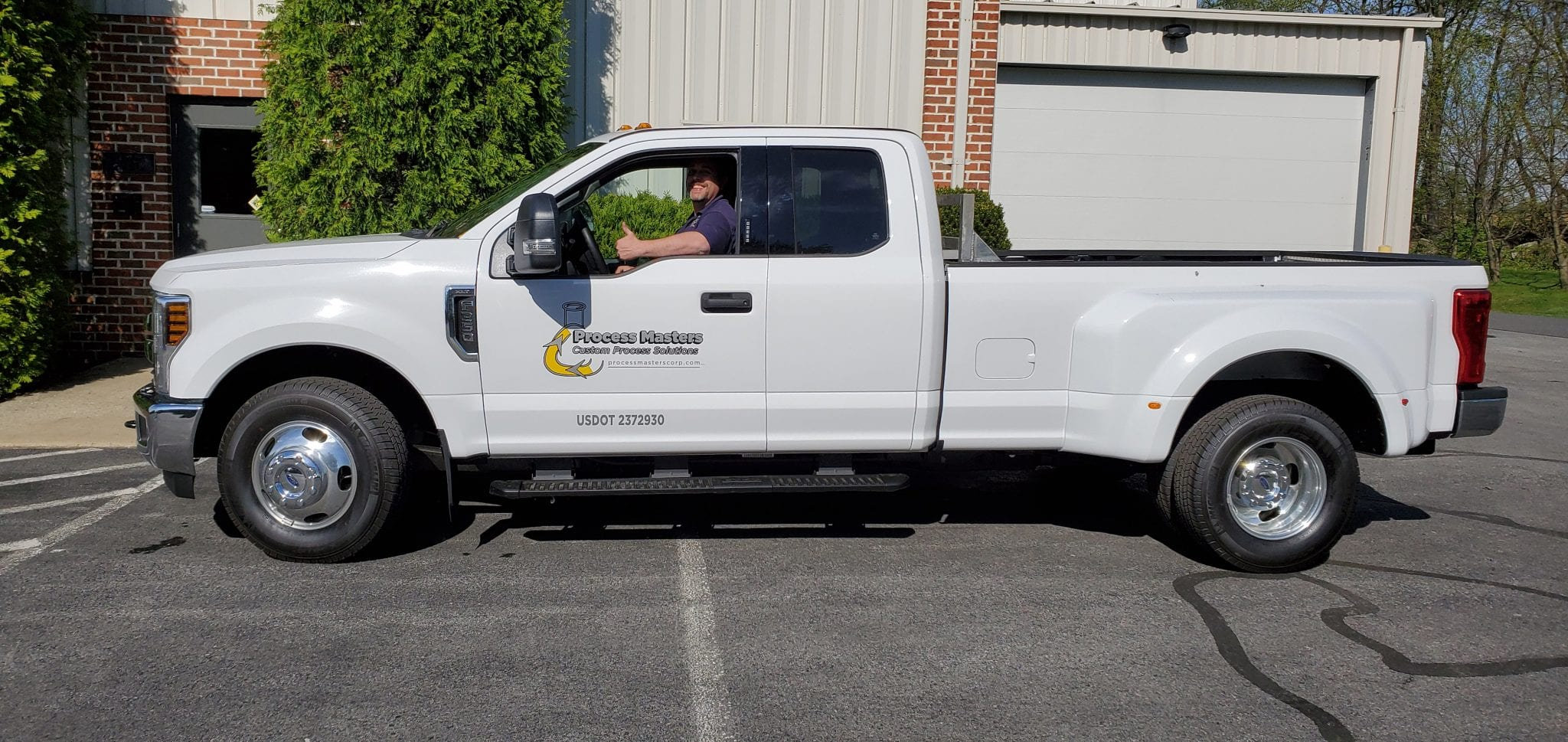 white work truck with Process Masters logo, happy driver giving thumbs up to camera