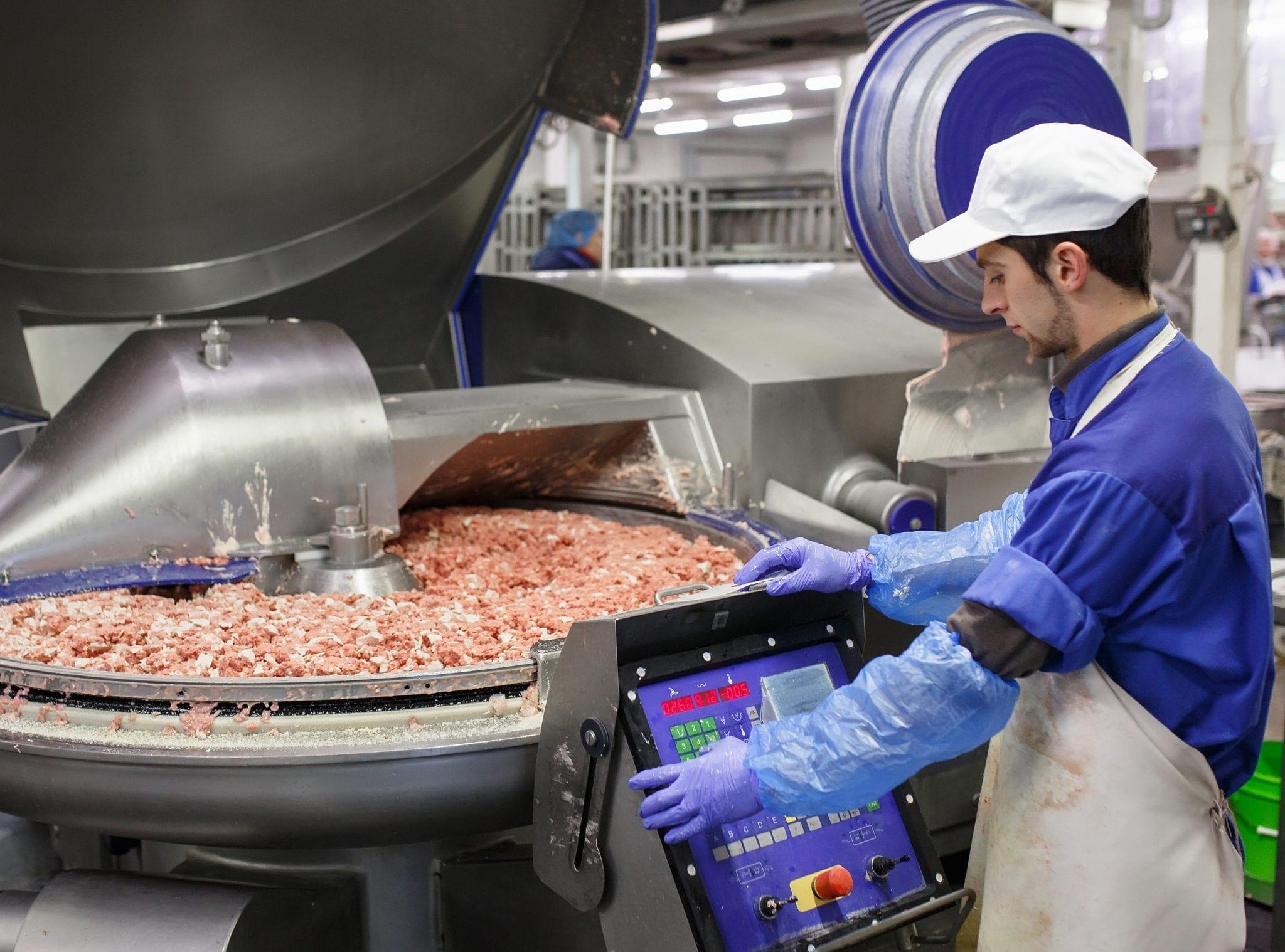 Meat industry photo worker standing over grinder