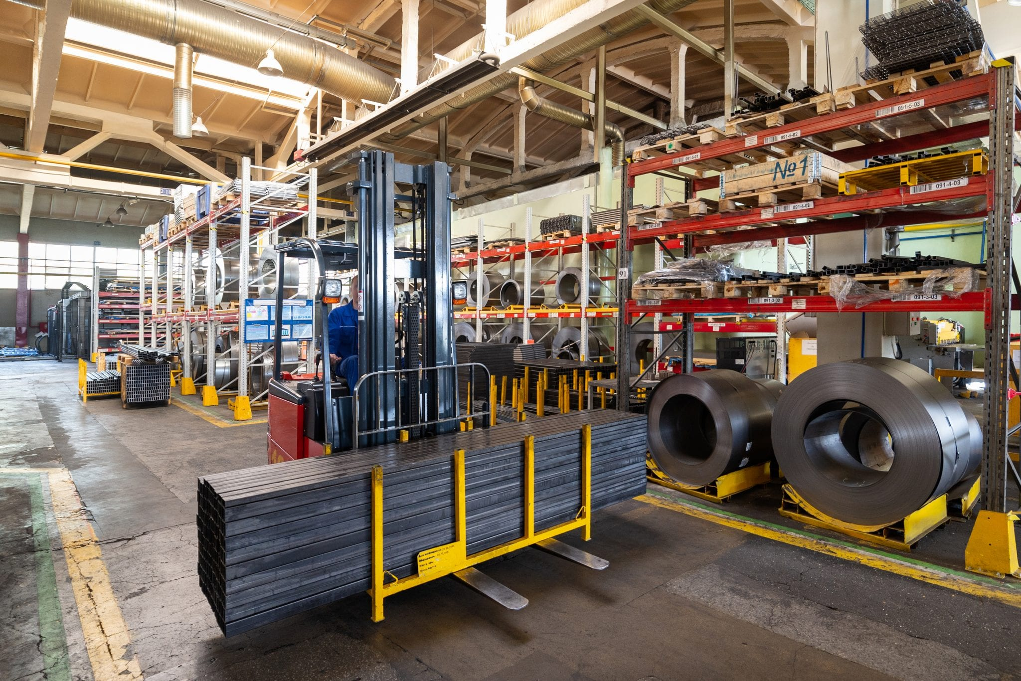 Factory stock wire. Wire rolled into coils lie on multi-tiered racks.